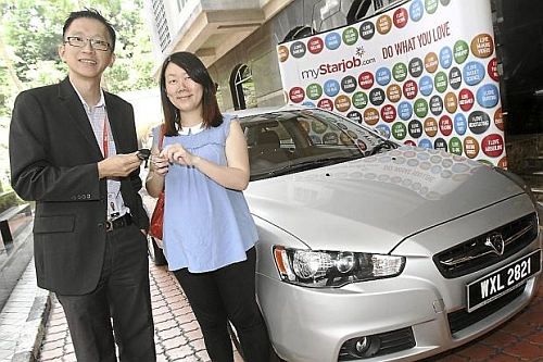 Lucky jobseeker: Tee receiving the keys to her Proton Inspira from Serm during the prize presentation ceremony at Menara Star in Petaling Jaya.