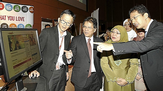 Up and running: Idris (second left) and Rohani checking out the website after the