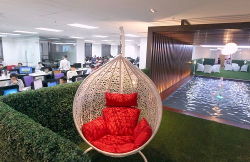 A discussion cum lounge area complete with faux grass, garden chairs and a water feature sits in the center of the office.