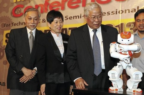 Pretty hi-tech: (From left) Abang Abdullah, Politeknik Kuching director Clara Ong and Manyin watching a dancing robot at the opening of the conference in Kuching. — ZULAZHAR SHEBLEE / The Star
